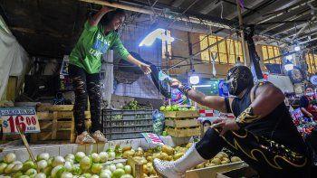 El luchador mexicano Ciclonico le da una máscara a una mujer mientras hace campaña para promover su uso en un mercado en Xochimilco, Ciudad de México, el 28 de agosto de 2020, en medio de la nueva pandemia de coronavirus.