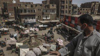 Ashraf Sayed, residente de la población de Monshah, donde hay un auge del coronavirus, contempla un mercado desde lo alto de un edificio en Sohag, Egipto, 2 de mayo de 2021.