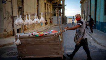 Un vendedor ambulante con una máscara como medida de precaución contra la propagación del coronavirus empuja su carro por una calle en La Habana, Cuba, el lunes 31 de agosto de 2020.