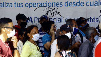 Personas esperan para ingresar a una agencia bancaria en Valencia, Venezuela, en la primera semana de la flexibilización de la cuarentena por el coronavirus COVID-19.