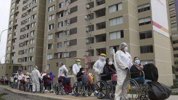En esta imagen, tomada el 21 de septiembre de 2020, trabajadores llevan en silla de ruedas a un grupo de unos 80 pacientes con COVID-19 que, tras recibir el alta, abandonan la que fuera la villa de los deportistas durante los Juegos Paramericanos de Lima, que ahora se utiliza como hospital de campaña para atender a cientos de enfermos de coronavirus, en Lima, Perú.