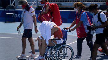 La española Paula Badosa sale de la cancha en una silla de rueda tras sentirse indipuesta durante un partido de cuartos de final del torneo de tenis de los Juegos Olímpicos de Tokio
