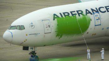 En esta foto proveída por Greenpeace, activistas de la agrupación ecologista pintan el costado de un Boeing 777 de Air France que estaba estacionado sin pasajeros en el aeropuerto Charles de Gaulle, al norte de París, el viernes, 5 de marzo del 2021.