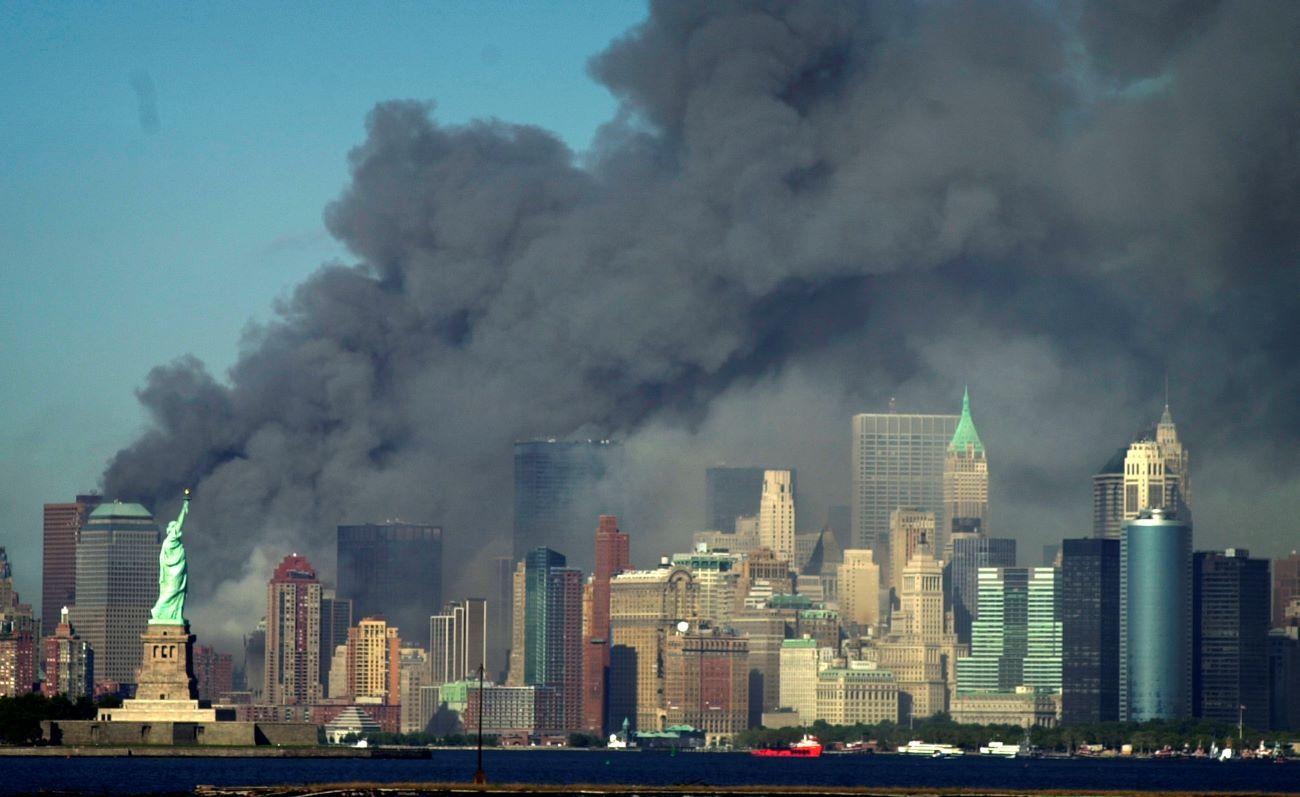 El humo se eleva hacia al cielo detrás de la Estatua de la Libertad donde estaba el World Trade Center, el martes 11 de septiembre de 2001.