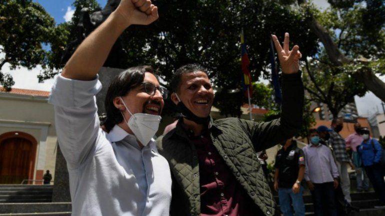 El recientemente indultado y liberado diputado opositor Gilber Caro (derecha) muestra el letrero de la Victoria junto al diputado opositor Freddy Guevara