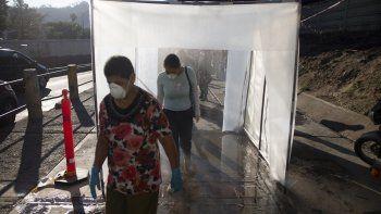 En esta fotografía de archivo del 18 de marzo de 2020, personas con mascarillas protectoras y guantes plásticos caminan por una cámara de descontaminación. Muchos venezolanos se resisten a hacerse la prueba del nuevo coronavirus por temor a ser encerrados en centros obligatorios de aislamiento si se descubre que están infectados.