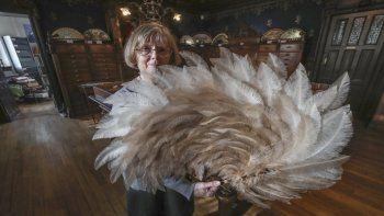 Anne Hoguet, de 74 años, artesana de abanicos y directora del Museo del Abanico de París posa con un abanico de plumas en el museo en París, el miércoles 20 de enero de 2021. El Musee de lEventail de París está en peligro de desaparecer por la pandemia.