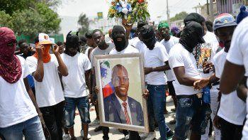 Miembros de una pandilla encabezada por Jimmy Cherizier, alias Berbecue, un expolicía que encabeza una coalición de pandillas llamada Familia G9 y Aliados, transportan un retrato del asesinado presidente Jovenel MoÍse durante una marcha efectuada el lunes 26 de julio de 2021 en el vecindario de La Saline en Puerto Príncipe, Haití, para exigir justicia tras el magnicidio