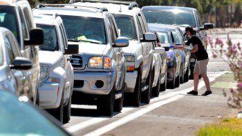 Personas hacen fila en sus vehículos para someterse a una prueba de COVID-19 en un centro de pruebas organizado por la organización de justicia para los migrantes Puente Movement, el sábado 20 de junio de 2020, en Phoenix.