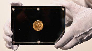 En esta foto de archivo tomada el 11 de marzo de 2021, un empleado de Sothebys sostiene una moneda Double Eagle de 1933 durante la subasta en vivo Tres tesoros - Coleccionada por Stuart Weitzman, de tres tesoros de la colección personal del diseñador y coleccionista de moda.