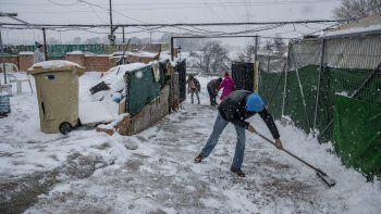 Unas personas palean la nieve en La Cañada Real Galiana, un enorme barrio pobre a las afueras de Madrid, España, considerado uno de los más grandes de Europa, el 8 de enero de 2021.