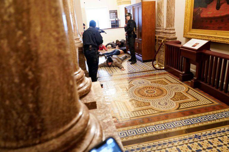 Agentes de la policía del Capitolio retienen a punta de pistola a unos manifestantes cerca del recinto de la Cámara de Representantes