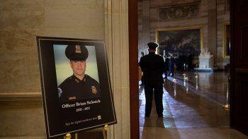 Una imagen del difunto policía del Capitolio de Estados Unidos Brian Sicknick, mientras la gente espera a que una urna con sus restos cremados sea llevada al Capitolio para ser depositada allí.