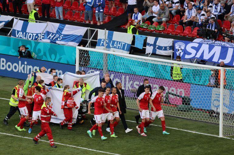 Los jugadores acompañan a los paramédicos mientras el mediocampista danés Christian Eriksen es evacuado del campo durante el partido de fútbol del Grupo B de la UEFA EURO 2020 entre Dinamarca y Finlandia
