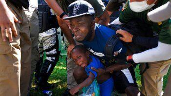 La Guardia Nacional Mexicana detiene a uno de los migrantes haitiano y a su hijo mientras caminaban por una carretera en Escuintla, estado de Chiapas, México, el jueves 2 de septiembre de 2021, en su viaje hacia Estados Unidos.