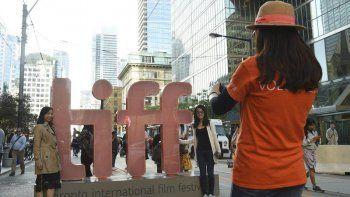 En esta fotografía del 5 de septiembre de 2019, un voluntario toma una foto a dos personas junto a una reproducción del logotipo del Festival Internacional de Cine de Toronto.