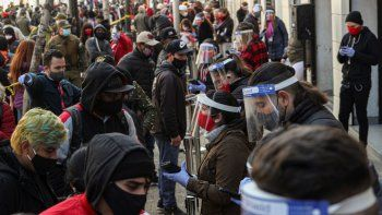 Empleados del gobierno usando mascarillas y caretas para protegerse del nuevo coronavirus ayudan a que la gente procese su retiro de un porcentaje de sus fondos de ahorro para el retiro en Santiago de Chile el jueves 30 de julio de 2020.