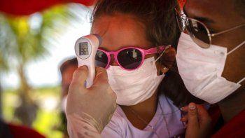 A una niña con mascarilla para protegerse del nuevo coronavirus le toman la temperatura en un puesto de control policial en la entrada de la provincia de La Habana, Cuba, el lunes 10 de agosto de 2020.