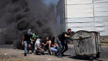 Manifestantes palestinos se guarecen durante enfrentamientos con fuerzas israelíes el viernes 14 de mayo de 2021 en el retén de Hawara, al sur de la ciudad cisjordana de Nablus.