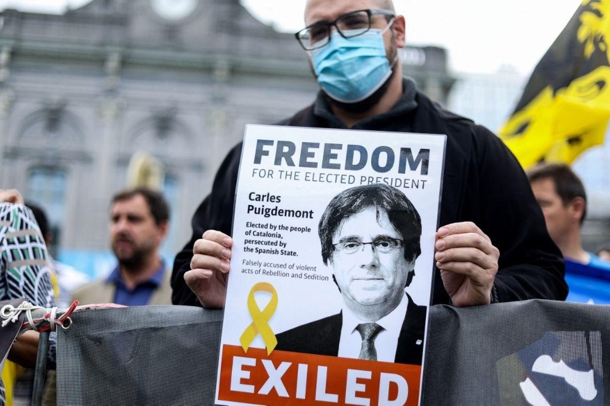 Un manifestante sostiene un volante que representa al expresidente catalán Carles Puigdemont durante una manifestación cerca del Parlamento Europeo en Bruselas, el 24 de septiembre de 2021 después de que el político exiliado fuera arrestado en Italia.