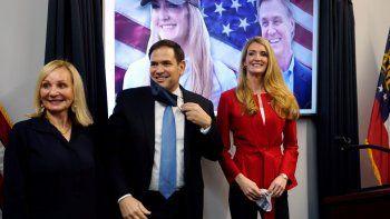 El senador republicano Marco Rubio aparece flanqueado por la candidata a senadora por Georgia Kelly Loeffler, derecha, y Bonnie esposa del senador David Perdue, tras un acto de campaña el miércoles 11 de noviembre de 2020 en Martietta, Georgia.