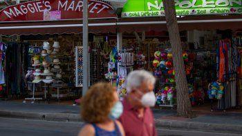 Los turistas que llevan máscaras faciales pasan por las tiendas de Palmanova en la isla de Mallorca el 27 de julio de 2020. El operador turístico TUI ha cancelado todas las vacaciones británicas a España continental desde hoy hasta el 9 de agosto, después de la decisión del gobierno del Reino Unido de exigir a los viajeros que regresen del país a cuarentena.