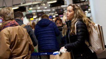La estadounidense Christine Barto hace fila para preguntarle sobre su vuelo a un representante en un mostrador de United Airlines en el aeropuerto internacional de Bruselas, el jueves 12 de marzo de 2020.