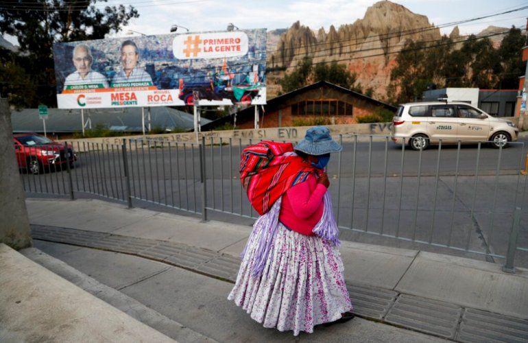 Una mujer camina cerca de un cartel del candidato presidencial Carlos Mesa