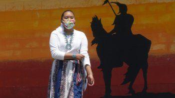 La estudiante Lemiley Lane, que utiliza mascarilla para protegerse del coronavirus y creció en la Navajo Nation en Arizona, camina cerca de un mural de un hombre indígena que representa a su secundaria en Bountiful, Utah, el 21 de julio de 2010.