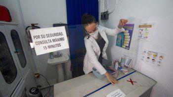Karla Hitzuri Montano, médico cirujana, con máscara protectora y anteojos, coloca una protección plástica para evitar el contacto con los pacientes en su consultorio médico y farmacia de propiedad en un barrio de la Ciudad de México el 4 de febrero de 2021.