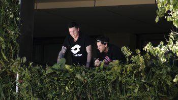 Dominic Thiem (derecha) aparece acompañado por un hombre no identificado en el balcón de su residencia en Adelaida, Australia, el martes 19 de enero de 2021.