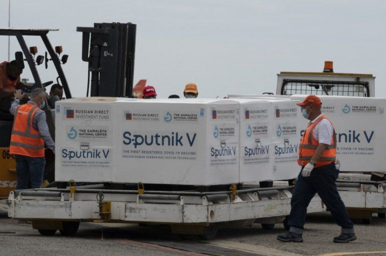 Venezuelan airport workers place in a refrigerated truck packages containing 100