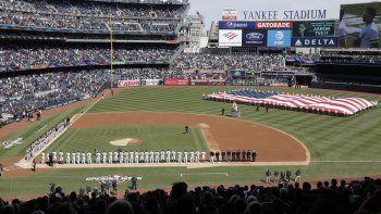 En foto de archivo del 28 de marzo del 2019, despliegan la bandera durante el Himno Nacional en el primer día de juegos de los Yanquis de Nueva York ante los Orioles de Baltimore. El 9 de abril del 2020 Forbes estimó que los Yanquis son el equipo más valioso de la MLB con 5 mil millones de dólares.