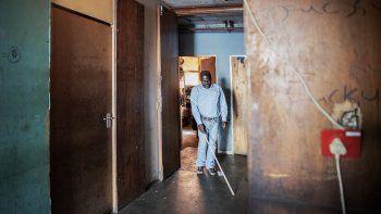 Jetro Gonese, de 60 años, una persona ciega de Zimbabwe, camina por el pasillo del edificio en el que vive mientras usa su bastón blanco, en el CBD de Johannesburgo, el 22 de junio de 2020.