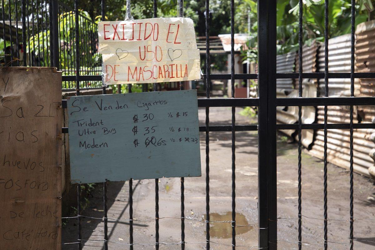 Un letrero en el que se exige el uso de mascarilla durante la pandemia de COVID-19 cuelga en un portón a la entrada de una zona habitacional en Managua, Nicaragua, el jueves 9 de septiembre de 2021. Otros letreros anuncian la venta de cigarrillos, huevo, cerillos, leche y café.