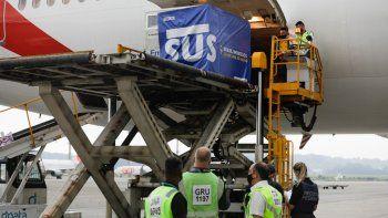 Un contenedor con vacunas contra el COVID-19 fabricadas por Oxford/AstraZeneca es bajado del avión a su llegada procedente de India en el aeropuerto internacional en Sao Paulo, Brasil, el viernes 22 de enero de 2021