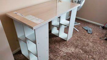 En esta foto proveída por Megan Fry, un escritorio armado con la superficie de una mesa y estantes de libros es visto en su casa en Indianápolis el 14 de septiembre del 2020.