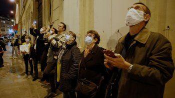 Transeúntes escuchan al tenor francés Stephane Senechal mientras canta al anochecer desde su apartamento durante la cuarentena impuesta por la pandemia de coronavirus en París, Francia, el lunes 9 de noviembre de 2020.