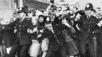 En esta foto de archivo tomada el 26 de octubre de 1965, los fanáticos del grupo británico The Beatles son retenidos por la policía en la cerca del Palacio de Buckingham, en el centro de Londres, durante una aparición pública del grupo cuando fueron recibidos por la reina Isabel II de Gran Bretaña.