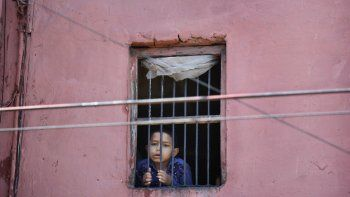 Un niño mira por la ventana de su casa en el barrio viejo de Nueva Delhi, India, 27 de marzo de 2020. Oxfan dijo el jueves 9 de abril de 2020 que el impacto económico de la pandemia de coronavirus podría arrojar a 500 millones de personas a la pobreza en el mundo.
