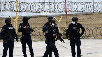 Agentes policiales de la unidad TIGRES montan guardia mientras un avión de la DEA extradita al presunto narcotraficante hondureño José del Tránsito García Teruel mientras se prepara para despegar, en el aeropuerto internacional Toncontín de Tegucigalpa, el 26 de febrero de 2021.