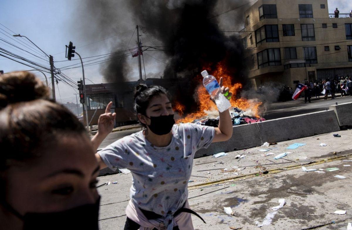 Un campamento improvisado de migrantes venezolanos arde después de ser incendiado por manifestantes durante una marcha de protesta contra la migración ilegal en Iquique, Chile, el 25 de septiembre de 2021.