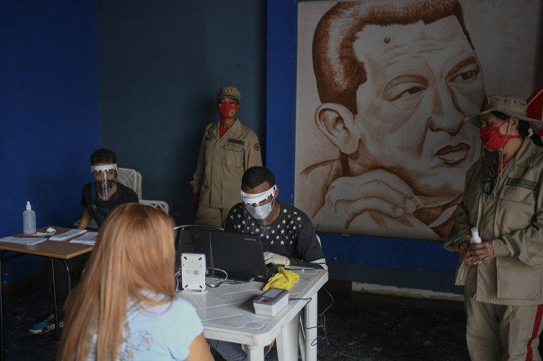 Personal del consejo electoral con equipo protector del coronavirus revisa archivos en Caracas con miras a las elecciones legislativas del 6 de diciembre. Detrás suyo hay una imagen de Hugo Chávez. Foto del 25 de julio del 2020.