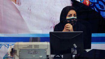 Bajo un retrato del difunto fundador de la República Islámica de Irán Ayatola Khomeini, una miembro del personal de la oficina de elecciones se apresta a registrar candidatos para le elección presidencial del 18 de junio, en Teherán, el martes, 11 de mayo del 2021.