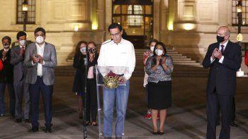 El presidente de Perú, Martín Vizcarra, baja la mirada mientras miembros de su gabinete lo aplauden frente al palacio presidencia en Lima, después de que el Congreso aprobó su destitución el lunes 9 de noviembre de 2020