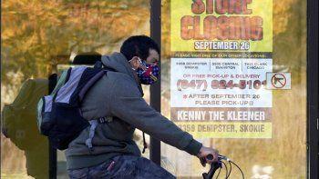 En esta foto del 6 de noviembre del 2020, un hombre pasa en su bicicleta junto a un negocio cerrado en Wilmette, Illinois. Con más encierros inminentes y meses antes de la amplia distribución de una vacuna, gobernadores en Estados Unidos están pidiendo más ayuda federal para el que se anuncia como un invierno sombrío.