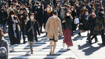 Decenas de personas con mascarillas para frenar la propagación del coronavirus cruzan una intersección concurrida del distrito comercial de Shibuya, en Tokio, el sábado 26 de diciembre de 2020