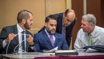 Pablo Ibar (cen.) escucha a sus abogados Joe Nascimento (izq.), Kevin J. Kulik (der.), y Benjamin Waxman (de pie) durante una audiencia en un tribunal en Fort Lauderdale, en el condado Broward, en Florida.