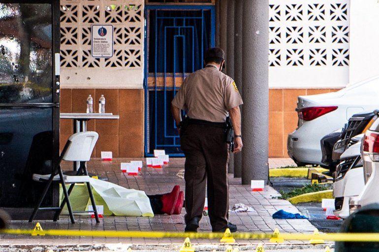 Se ve un cadáver cerca de las puertas de un club de billar que fue alquilado para un concierto después de que tres hombres armados mataron a dos personas e hirieron al menos a 20 personas en el área de Hialeah