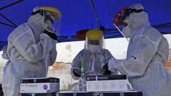 Trabajadores de la salud bolivianos preparan el equipo para realizar pruebas a las personas en la Piscina Olímpica de La Paz, el 6 de enero de 2021. El gobierno boliviano inauguró el 6 de enero un centro de diagnóstico de COVID-19 autocine en la Piscina Olímpica, donde los trabajadores de salud harán pruebas de PCR a todos aquellos que presenten síntomas.